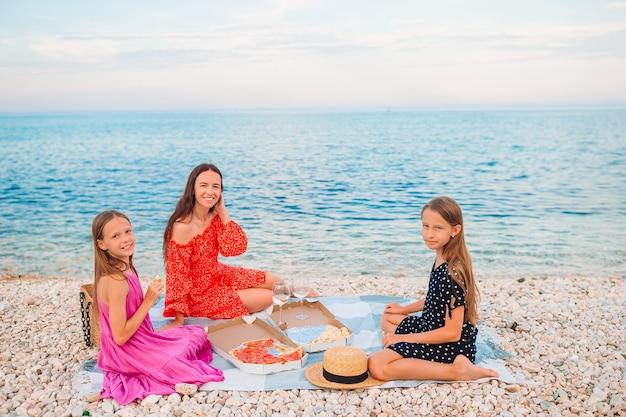 ピクニックのビーチで子供と幸せな母 Premium写真