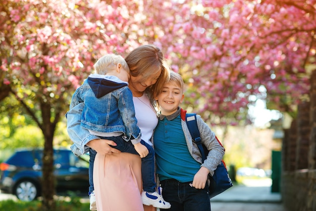 Happy mother with kids on the walk in spring city. mother and children hugging outdoors. Premium Photo