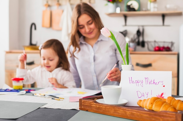 Happy mothers day inscription on table near painting daughter and mother Free Photo