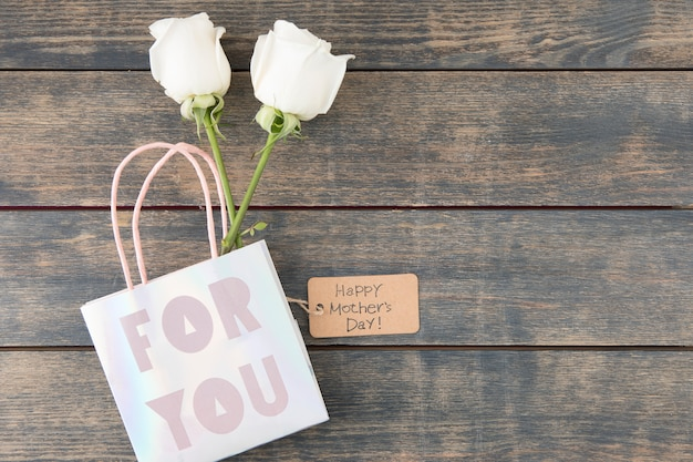 Happy mothers day inscription with roses in paper bag Free Photo