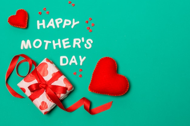 Happy mothers day title near hearts and gift box Free Photo