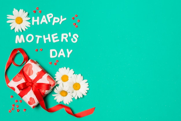 Happy mothers day title near white flowers and gift box Free Photo