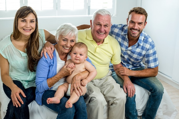 Happy multi-generation family on bed at home Premium Photo