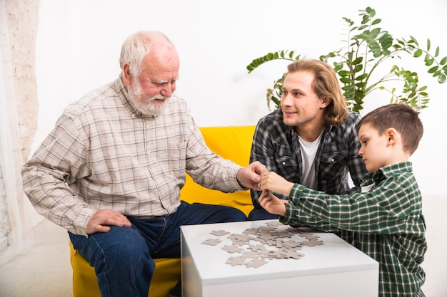 Happy multi-generational family assembling jigsaw puzzle together Free Photo