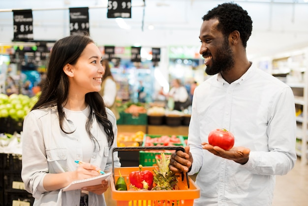 Happy multiethnical couple choosing goods in supermarket Free Photo
