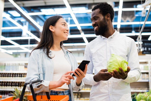 Happy multiracial couple choosing goods and looking at each other in supermarket Free Photo