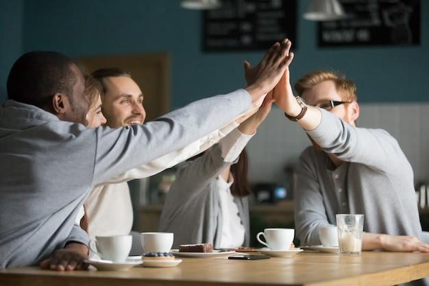 カフェでの会議でハイファイブを与える幸せな多民族の友達カフェ 無料写真