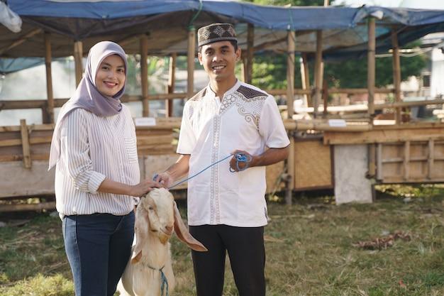Счастливая мусульманская пара покупает козу для жертвоприношения ид адха или праздника курбан Premium Фотографии