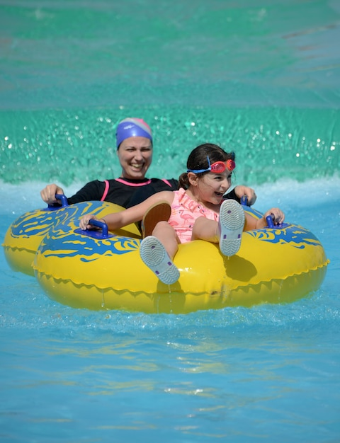 A happy muslim family of mother and daughter in swimming pool Premium Photo