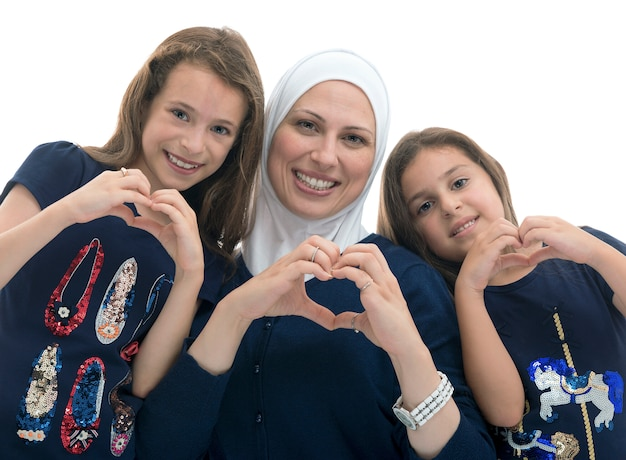 Happy muslim family, mother and her daughters with heart love sign Premium Photo
