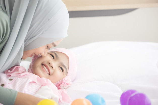 Happy muslim mother cuddling with her daughter on the bed Premium Photo