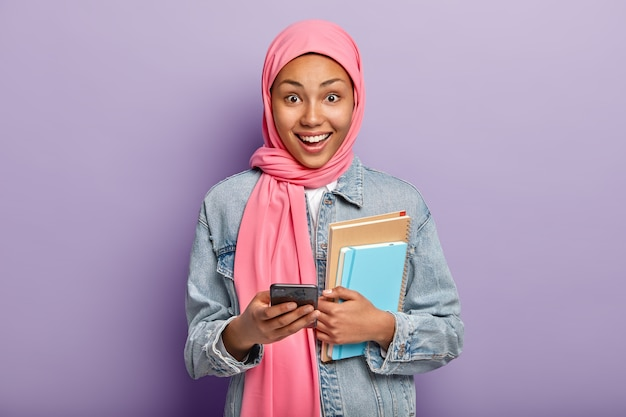 Happy muslim woman advanced user of technology holds notepads and cellular, wears pink veil on head Free Photo
