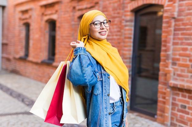 ショッピングモールの後に買い物袋を持つ幸せなイスラム教徒の女性 Premium写真