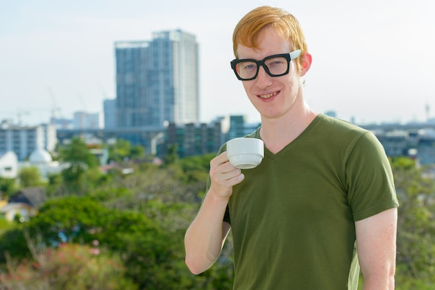 Счастливый ботаник с рыжими волосами пьет кофе на фоне города Premium Фотографии