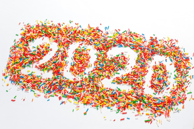 Happy new 2020 year. colorful number shape with bright rainbow sugar sprinkles isolated on white Free Photo