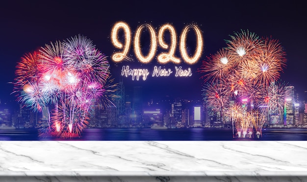 Happy new year 2020 (3d rendering) fireworks over cityscape at night with empty white marble table Premium Photo