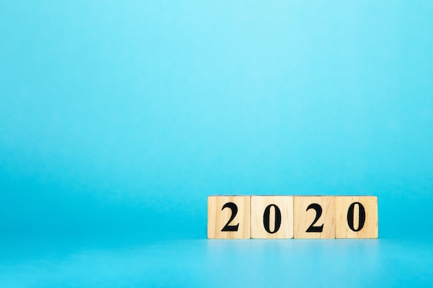 Happy new year 2020 concept with wooden block cube on blue Premium Photo