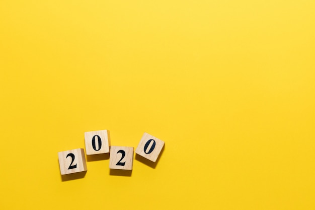 Happy new year 2020 concept with wooden block cube on yellow Premium Photo
