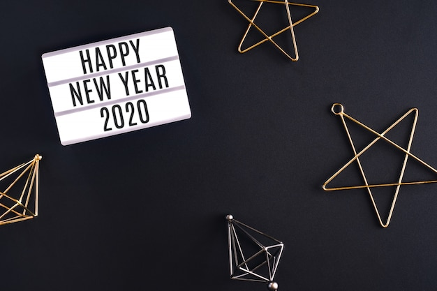 Happy new year 2020 party light box with star decoration item top view on black background table Premium Photo