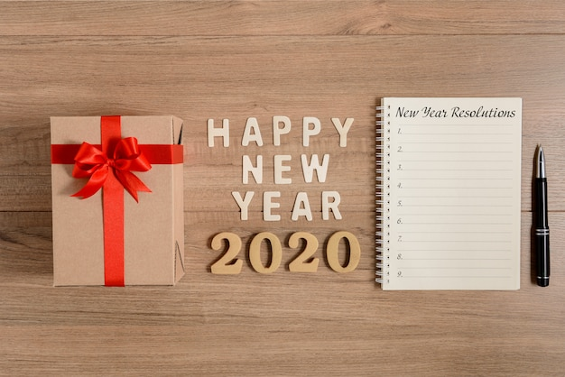 Happy new year 2020 wood and new year's resolutions list written Premium Photo