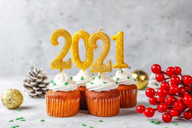 Happy new year 2021, cupcakes with golden candles. Free Photo