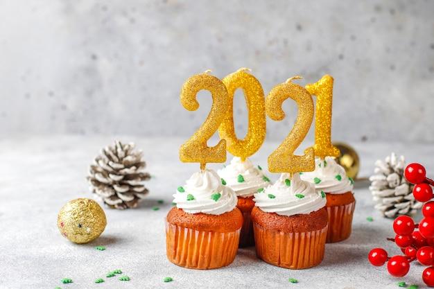 새해 복 많이 받으세요 2021, 황금 촛불 컵 케이크. 무료 사진