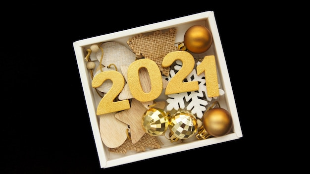 Happy new year 2021. golden numbers 2021 with golden christmas balls in black box Premium Photo