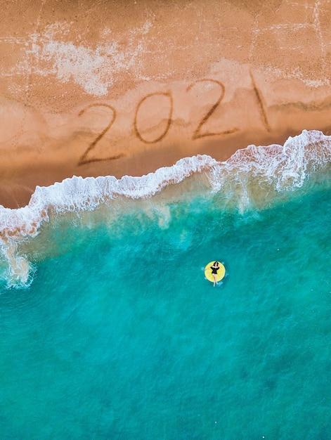 С новым годом 2021 года, надпись на пляже с волной и синим морем. Premium Фотографии