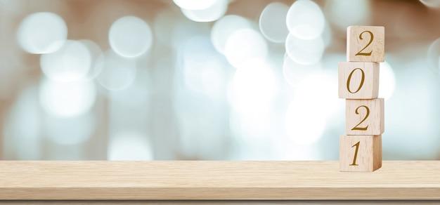 С новым годом 2021 на деревянном кубическом блоке и размытом абстрактном боке светлом фоне Premium Фотографии