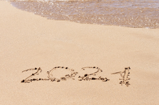 Happy new year 2021 text on the beach. planning vacation. Photo | Premium Download