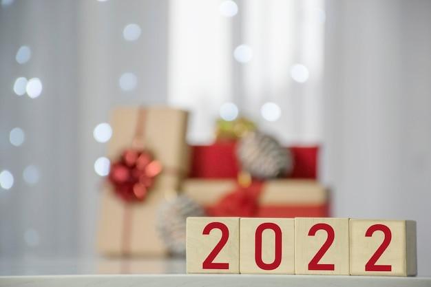 행복 한 새 해 2022 선물 상자와 배경에 흐리게 Bokeh 빛 나무 큐브 블록에. 겨울 방학 및 크리스마스 인사말 카드입니다. 프리미엄 사진