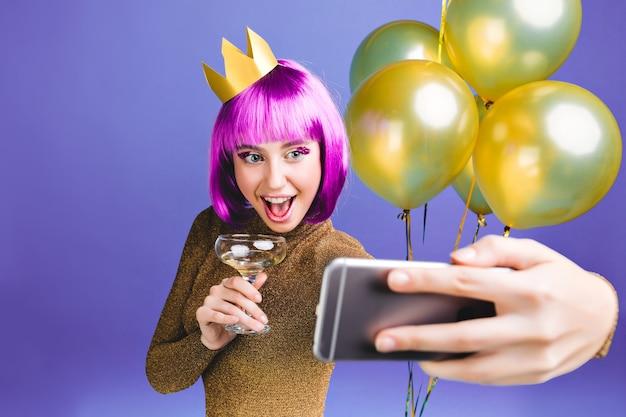 Selfieの肖像画を作るピンクのヘアカットで興奮した若い女性の幸せな新年のお祝いの瞬間。豪華なドレス、黄金の風船、飲酒カクテル、誕生日パーティー。 無料写真