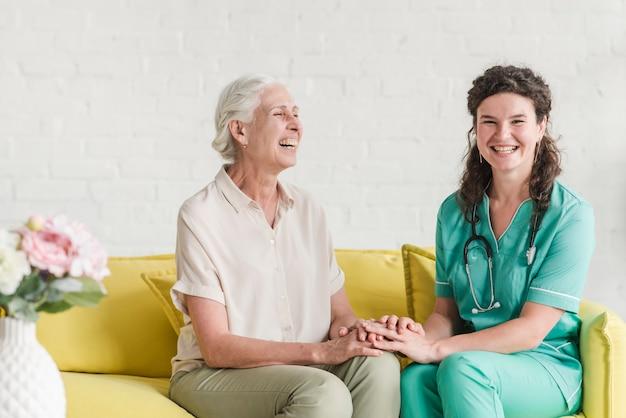 Happy nurse and senior woman sitting on sofa holding hands Free Photo