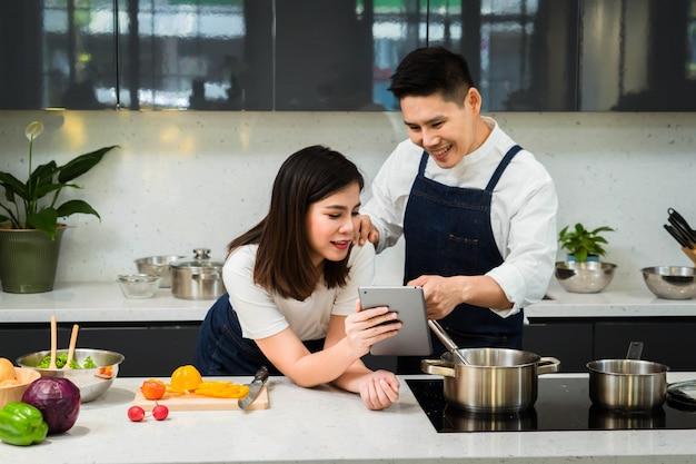 アジアカップルシェフのキッチンで料理に満足。 Premium写真