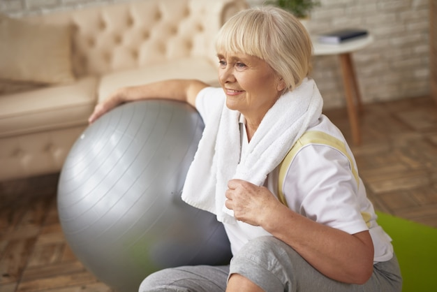 Happy old lady with fit ball workout recovery. Premium Photo