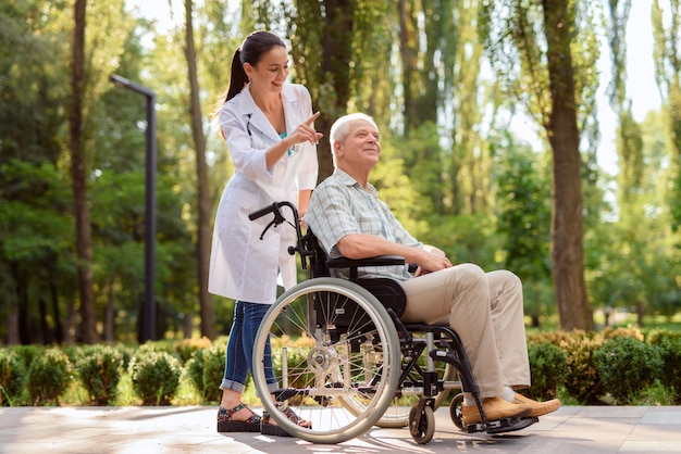 Happy old man in wheelchair in park with doctor Premium Photo