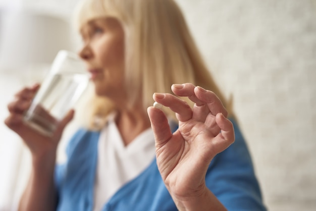 Happy old woman taking morning pills drinks water. Premium Photo