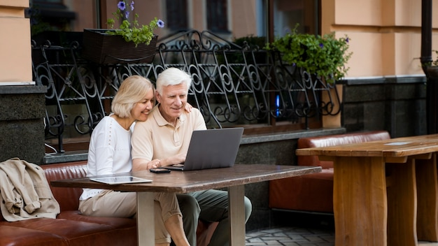 Счастливая пожилая пара, сидя на скамейке на открытом воздухе с ноутбуком Premium Фотографии