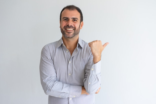 Happy optimistic handsome latin sales manager pointing aside and looking at camera. Free Photo