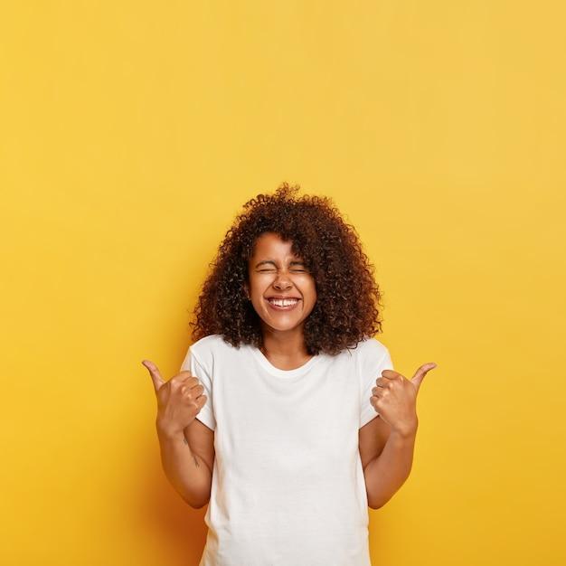 덥수룩 한 선명한 머리카락을 가진 행복한 민족 아가씨는 엄지 손가락으로 긍정적 인 대답을주고 멋진 아이디어를 좋아하며 웃음에서 눈을 감고 노란색 벽에 고립 된 모형 티셔츠를 입고 있습니다. 무료 사진