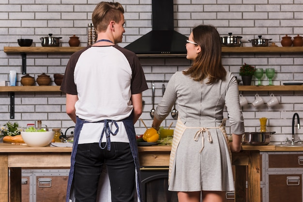 Happy pair cooking at table in kitchen Free Photo