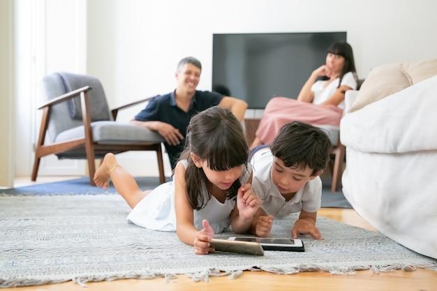 거실에서 바닥에 누워 디지털 기기를 함께 사용하는 어린 아이를 보는 행복한 부모. 무료 사진