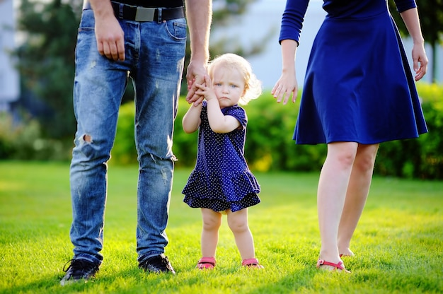 Happy parenthood: young parents with their sweet toddler girl in sunny park. Premium Photo