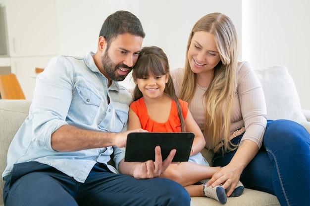 幸せな親とかわいい娘がソファに座って、ビデオ通話や映画鑑賞にタブレットを使用しています。 無料写真