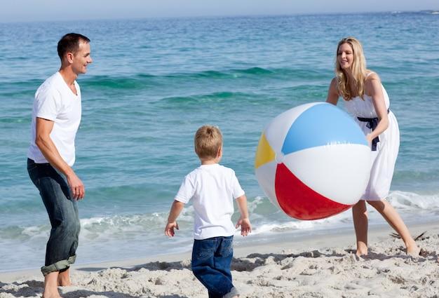 幸せな親とその息子がボールで遊んでいる Premium写真