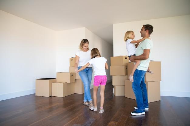 Счастливые родители и две девочки танцуют и веселятся возле кучи коробок во время переезда в новую квартиру Бесплатные Фотографии