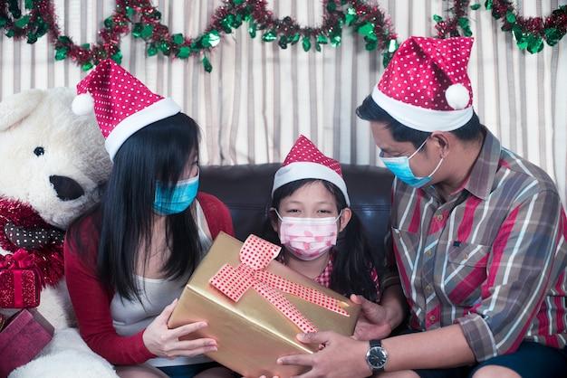 Счастливые родители, дающие рождественский подарок дочери с носить маску для лица. семья в интерьере рождества Premium Фотографии