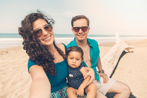 Happy parents smiling and taking selfie on beach . Free Photo