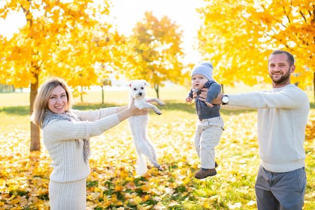 Счастливые родители с их ребенком и маленьким щенком, проводить время на природе в солнечный день Premium Фотографии