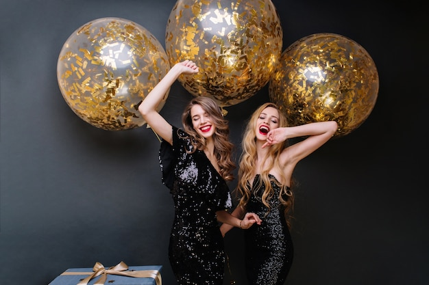Happy party moments of two fashionable funny young women. luxury black dress, red lips, long curly hair, brightful mood, having fun, big balloons with golden tinsels. Free Photo